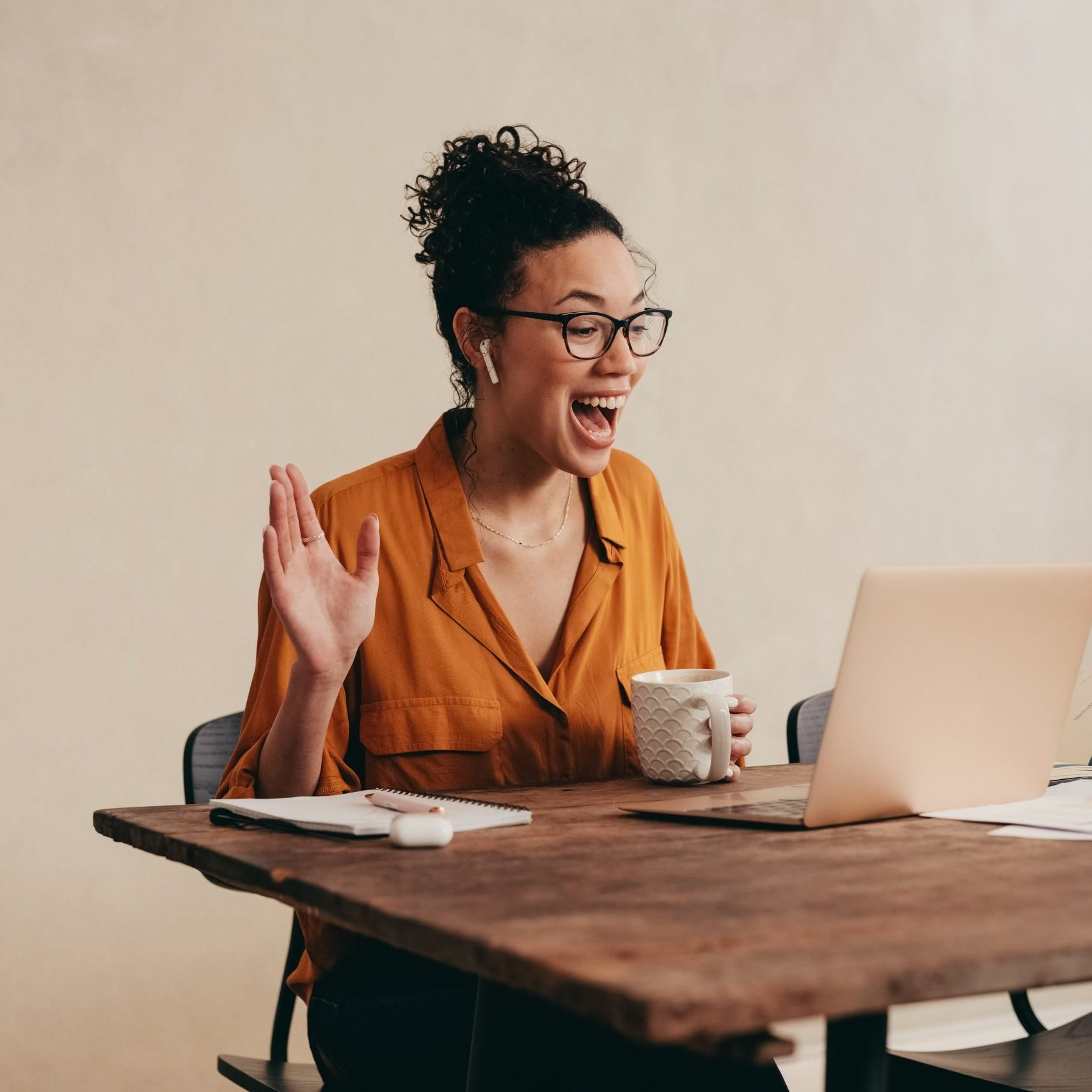 Young woman greeting colleagues on a video call. Business woman on a video conference call working from home.